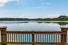 Railing of Fishing Pier with View of Stumpy Lake in Virginia Beach. Railing of fishing pier with a view of the lake at Stumpy Lake Natural Area in Virginia Beach Royalty Free Stock Photo
