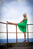 Railing Model. A beautiful blond model in a green dress posing on a seaside railing Royalty Free Stock Photos