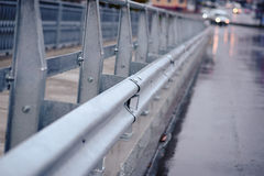 Railing near the wet road stock photography