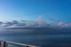 Railing sea view at night with blue ocean water stock photos