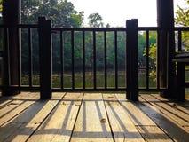 Railing shadow casting on vintage wooden balcony floor Stock Image