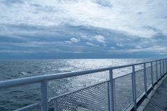 Railing on a ship`s upper deck, converging with the horizon and stunning blue sky in the distance stock photography