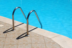 Railing stairs in the blue swimming pool Stock Images