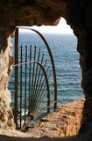Railings and ocean wall. Closeup of protective railings on ocean wall viewed though stone window Stock Image