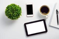 Raillez du bureau avec le PC blanc vide de comprimé d'écran, le pot noir de smartphone d'écran de blanc, de tasse de café, de car photo libre de droits