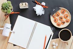 Raillez du carnet ouvert, des métiers de papier, du calendrier de cube, des carottes grillées avec le visage effrayant et de la t Images stock