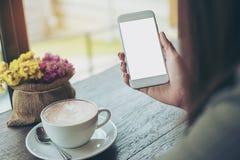 Raillez du téléphone intelligent avec du café chaud Image stock