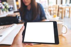 Raillez vers le haut de l'image d'une main tenant le PC noir de comprimé avec l'écran vide et la tasse de café blancs sur la tabl image stock
