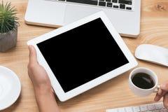 Raillez vers le haut de l'image d'une main tenant le PC noir de comprimé avec le blanc blanc photo libre de droits