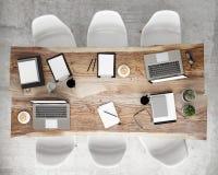 Raillez vers le haut de la table de conférence de réunion avec des accessoires de bureau et des ordinateurs portables, fond intér Image libre de droits
