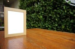 Raillez vers le haut du cadre blanc vide se tenant sur la table en bois dans le restaura de barre image stock