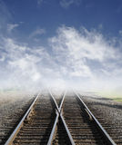 Railroad. Two railroad tracks lead off into the daylight foggy sky with clouds Royalty Free Stock Images