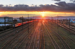 Railroad avec le train au coucher du soleil et à beaucoup de lignes photos stock