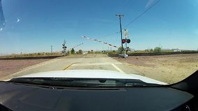 Opening barrier with semaphores after the train. Railroad barrier opens after train passes by stock footage