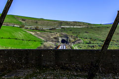 Railroad behind barbed wire and green hills Stock Image