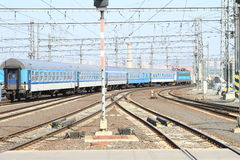 Railroad with blue train. Planty of rails of railroad with wiring and blue train Stock Photography