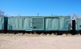 Railroad Boxcar Blues. A faded blue corrugated box car sits idly waiting for it's next load of freight and move onto it's next destination.  A clear blue sky Stock Image
