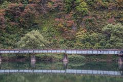 Railroad bridge in autumn. Iron railway bridge in autumn forest , Japan Stock Photo