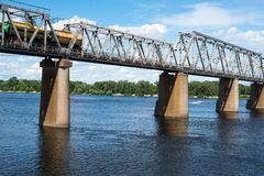 Railroad bridge in Kyiv across the Dnieper with freight train Stock Images