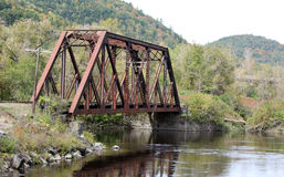 Railroad Bridge Over Water in Autumn. Old rusted railroad bridge with water beneath and mountains in the background. Just the beginning of Autumn and the leaves Stock Images