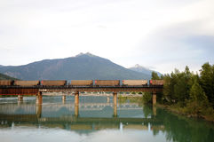 Railroad Bridge Revelstoke, Canada. Train crossing railroad bridge at Revelstoke, Canada leaves reflection on the Columbia River below Stock Photos