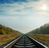Railroad closeup goes to horizon under cloudy sky Royalty Free Stock Image