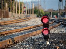 A railroad color position light flashing red stop lights with fe. A railroad color position light flashing red stop lights with some fencing to the left Stock Photo