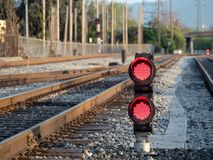 A railroad color position light sits ground level flashing red s. A railroad color position light sits on ground level flashing red stop lights Royalty Free Stock Photo