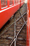 A railroad cross between two red trains Stock Photo