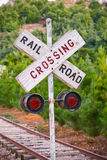 Railroad Crossing. Sign with tracks & trees in the distance. Shallow focus on the sign Stock Photos