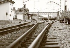 Railroad crossing. Crossing train tracks near a station with an empty train waiting to exit Stock Photo