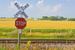 Railroad crossing. Sign in front of farmland Stock Image