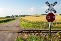 Railroad crossing. Roalroad crossing and stop sign in farmland Royalty Free Stock Photo