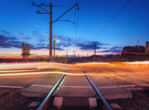 Railroad crossing with car lights in motion at night Royalty Free Stock Image