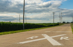 Railroad crossing in the country. Railroad crossing ahead sign painted on the pavement with rural Midwest landscape in background royalty free stock photo