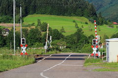 Railroad crossing with gates in German countryside Stock Photo