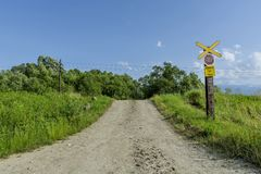 Railroad crossing with the dirt road and old stop sign Stock Photo
