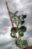 Railroad crossing lights and barricade. Railroad crossing sign, lights and barricade against cloudy sky Stock Photo