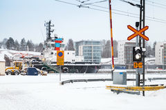 Railroad crossing near port in snowy winter day stock images