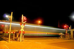 Railroad crossing at night with a Metro Stock Photo