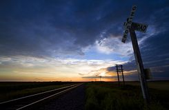 Railroad crossing in North Dakota. The railroad tracks stretch in the distance during a sunset in eastern North Dakota Stock Photo