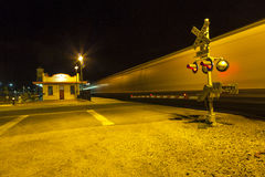 Railroad crossing with passing train by night Royalty Free Stock Image
