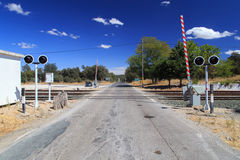 Railroad crossing. In rural area under blue sky. Can be used as metaphor for standing at a crossroads stock images
