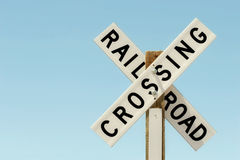 Railroad crossing sign. On wood against a light, clear blue sky royalty free stock images