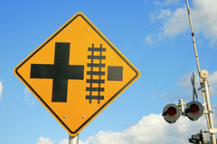Railroad crossing sign. With lights and arm in background on blue sky with clouds Royalty Free Stock Image