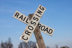 Railroad Crossing Sign Against Blue Sky. White Railroad Crossing Sign Against Blue Sky Stock Image