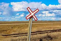 Railroad crossing sign along gravel road.  Stock Image