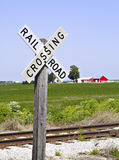 Railroad Crossing Sign III. An old-fashioned railroad crossing sign with a farm scene in the background stock photography