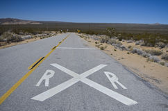 Railroad Crossing. Sign painted on desert road Royalty Free Stock Photos
