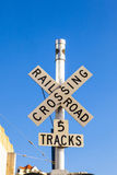 Railroad crossing sign under blue sky Stock Photo